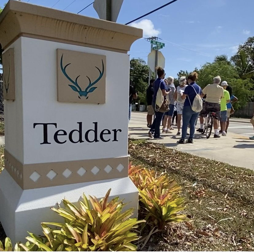 Attendees stand on a sidewalk in the background, a Tedder community sign sits in the foreground.